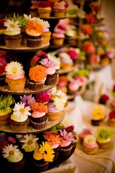 Iced cupcakes decorated with real flowers. Could be pretty with bright fall colors