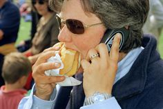 GB. England. Badminton Horse Trials. A women talks on her mobile phone. 1999.   I like how the image has a witty feel to it and that the model is unexspected and natural.   This image is a good representation of society today, through the use of fast-food and a mobile phone