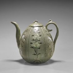 Korean inalid celadon glazed stoneware ewer; of ovoid form with molded coiled handle and tall spout; inlaid floral designs to somewhat paneled body; matching cover with curly-q finial (old repairs to cover); H: 7 1/2""
