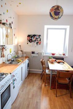 Helle Küche mit Essbereich in saniertem Altbau: Holztisch, weiße Wände, Farbakzente, großes Fenster.  #bright #kitchen #Holzdielen #Küche