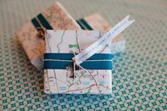 Wedding favors wrapped in map paper with cute airplane charm @myweddingdotcom
