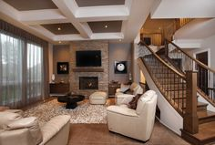 Le mobilier sobre du séjour permet de mettre en évidence le foyer à gaz, encastré dans un muret recouvert de pierre métallisée dans les teintes de beige, de gris et de brun, sur lequel est fixé un écran de télévision.