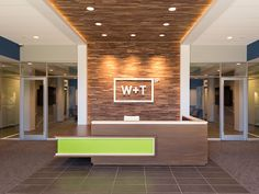 A modern reception desk with a vibrant Chroma accent welcomes visitors to this North Carolina law office. Office Reception Design, Modern Reception Desk, Corporate Office Design, Dental Office Design, Clinic Interior Design, Interior Design Photos, Lobby Interior, Law Office Decor, Counter Design
