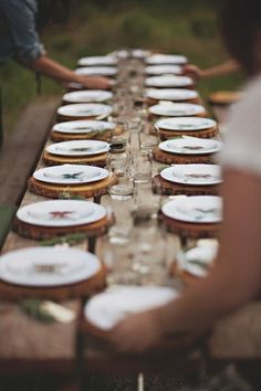 Rustic tablescape -- Wooden slab place settings beneath picturesque plateware, wooden tabletop