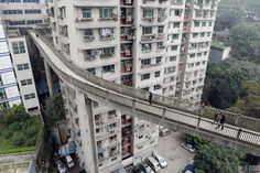 A pedestrian bridge between a street and a building's floor in Chongqing.Chongqing is known as mountain city in China In China, China Today, Passage Piéton, Chongqing China, Bridge Design, Pedestrian Bridge, Beaux Villages, High Rise Building, Brutalist