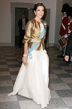 H.R.H. CROWN PRINCESS MARY OF DENMARK  Occupation: Wife of Crown Prince Frederik of Denmark, future King of Denmark; mother of four.    In a white gown, gold jacket, and tiara for a celebration of her mother-in-law's 40th anniversary on the Danish throne.