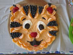 """Daniel Tiger Fruit Pizza! Created for Av's 3rd birthday Pillsbury Sugar Cookie Dough for base 1 c. cream cheese + 1 c. sugar + 1 t vanilla + orange food coloring Topped with blueberries, strawberries, clementine pieces Extra from making oreo balls for black parts of face (1 pkg oreos + 1 block cream cheese) Eye whites could be uncolored fruit pizza """"frosting"""" mixture held out....I had some extra from another dessert I made (cream cheese+ powdered sugar +cool whip) that I used for this one"""