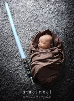 Another baby is dressed as a Jedi Knight, complete with the brown cloak and light saber...
