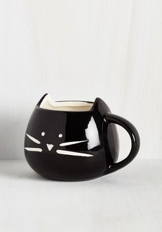 However you take your morning bevvie, it's always to your liking coming from this black mug! Starring a minimalist, whiskered face and a rim shaped into two pointed ears, this rounded ceramic cup is sure to leave you 'feline'