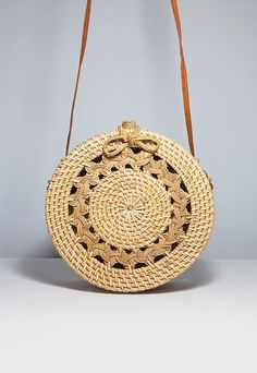 """This unique round bag is handwoven from Ata grass. It takes 1 women 1 month to weave to create the intricate woven pattern on the bag. Each basket is handwoven &""""smoked"""" over coconut husks, adding patina and strength. Features, woven """"Ata pattern"""" on thefront, plain on the back, leather shoulder strap with woven clip &... Read more"""