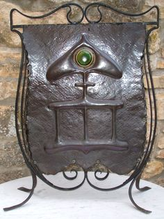 The cast iron fireplace with black marble hearth and ornate brass fire fender is finished with a companion set styled as a masted sailing ship with dragon prow, and copper Arts and Crafts fire screen depicting Siegfried the Viking.