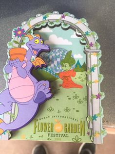"""Watering can design features the Sorcerer Mickey topiary depicted in front of Epcot's iconic ball Epcot Flower & Garden Festival 2016 Logo Magnetic back Wood 2"""" H x 4"""" W x 1/4"""" D new"""