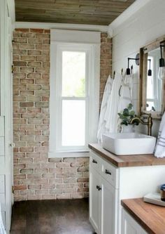 Vintage Inspired Farmhouse Bathroom Makeover 2019 Brick wall in bathroom love the white cabinets and butcher block countertops wood ceiling shiplap walls The post Vintage Inspired Farmhouse Bathroom Makeover 2019 appeared first on House ideas. Modern Farmhouse Bathroom, Farmhouse Décor, Farmhouse Design, Modern Bathrooms, Small Bathrooms, Farmhouse Ideas, Bathroom Renos, Master Bathroom, Bathroom Wall