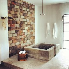 Cowboy concrete tub and rain shower in open concept loft style hotel room.