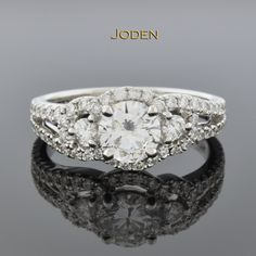 This beautiful engagement ring by Simon G. has subtle details of a three stone ring with just a hint of asymmetry all trimmed with brilliant diamonds.