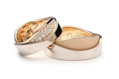 Deze trouwringen bestaan ieder uit twee ringen die over elkaar heen zijn geschoven. De herenring heeft een matte geelgouden onderring en een glanzende witgouden bovenring. Bij de damesring is de kleurstelling hetzelfde. Aan de bovenzijde van deze trouwring is een vlak met diamanten zichtbaar. Deze diamanten volgen de ovale contouren van de ring en zijn kleiner in de hoeken zodat het vlak perfect gevuld is.