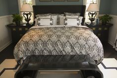 Dark bedroom set features black bedside tables, headboard, and scroll-style end table.