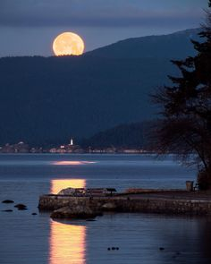"""Howlin' for You  . Thursday morning's """"Full Wolf Moon"""" sets directly over Lighthouse Park & Bowen Island. Captured from Second Beach in Stanley Park looking northwest over the Seawall at Ferguson Point and over English Bay to Point Atkinson in West Vancouver British Columbia Canada  January 12 2017"""