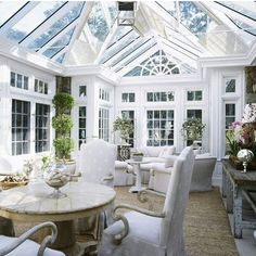 STYLISH SUNROOMS | Mark D. Sikes: love those plant stands! Use wicker, rattan, a fountain, stone tables, anything green & lush, wrought iron accents: bring the outside in.