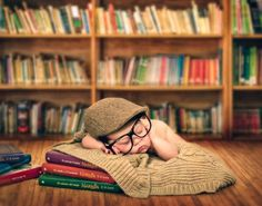 Infant with glasses and cap, sleeping on the Narnia books... LOVE this.