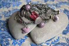Wikkelarmband gemaakt van leren (koeleer en buffelleer uit Azie) handgevlochten koorden. Voorzien van diverse metalen, zilveren knopen,kralen en bedels aangevuld met diverse gekleurde knopen en kralen.
