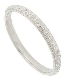 This finely engraved antique style wedding ring is crafted of platinum from the original antique ring. A repeating pattern of full figured blossoms weave across the face of this beautiful ring. The wedding ring measures 2.12 mm in width. Size 7 1/2. We can re-size one size larger or smaller.  Also available in 14K or 18K yellow and white gold. Actual prices depend on current market value of the precious metal used.