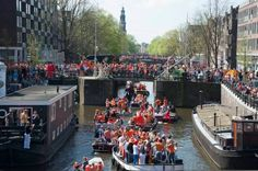 Queensday 2012 in the Netherlands - Amsterdam Canals filled with boats and orange dressed people!