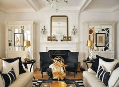 A striking Art Deco style living room in the key shades of black and white with gold accents to break up the monochrome look.