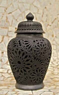 Este es el Barro Negro de Oaxaca. Este objeto es una hermosa olla con estampados de flores a lo largo de todo el asunto.