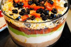 Seven Layer Dip VI Recipe. 1. Bean dip 2. Sour cream 3. Guacamole 4. Salsa 5. Cheddar cheese 6. Lettuce 7. Green onions/ tomatoes/ olives optional