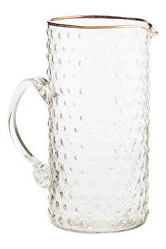 Jarra en vidrio con relieve: Jarra de vidrio con superficie con relieve y borde dorado. Diámetro superior 9 cm, alto 19,5 cm. Capacidad aprox. 1,1 litros.