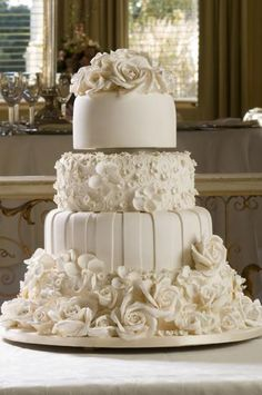 White wedding cake, but think with real red roses at the bottom, gold stripes, purples orchids, and black lace around the top one..... mmmmmmm decadent elegance!