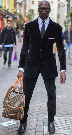 man in black dressed very well with very ugly bag