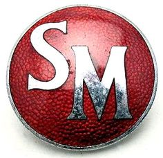 Singer Car Badge - 1948 – 1954 Singer SM1500 4 door with the 1497cc or 1,506cc overhead cam engine. This simple badge is 45mm in diameter with SM (Singer Motors) in a red background. Marked J. Fray - B/ham.