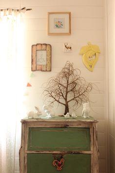 Les détails d'une chambre champêtre : les petits animaux blancs, les tableaux aux teintes douces, et la branche pour accrocher les rideaux en voilage légers