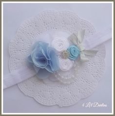 """"""" Ella """"   Made to Match any beautiful Cinderella gown, this special headband features a delicate blue chiffon rosette and handmade satin roses. A touch of bling makes this headband fit for a princess.  This headband is available on a soft elastic headband in your choice of size, or also on a satin covered alice style headband.    Find Ella Here : http://4lildarlins.com/catalog.php?item=659"""