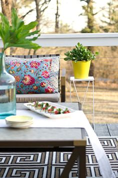 Colorful throw pillows and a succulent plant in a yellow pot decorate a backyard…