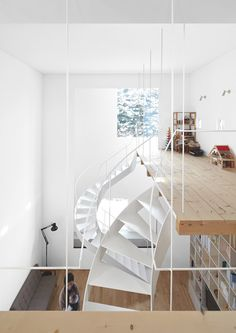 A wooden ladder and a pair of winding steel staircases link the rooms of this lofty house in Sapporo, Japan
