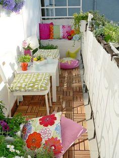 balkon gestalten pflanzen farbige dekokissen