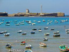 Desde la playa de La Caleta, se ven las barcas de los pescadores, los mismos que también encontramos por las calles del barrio La Viña en Cadiz, vendiendo las capturas del día.  Al fondo protegiendo la bahía desde el 1700, parte del castillo de San Sebastian, y la avanzada de Santa Isabel.