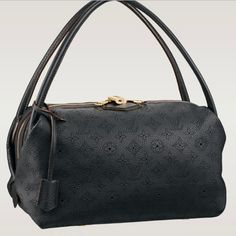 - Calfskin leather trimmings - Subtle shiny golden brass hardware - Elegant interpretation of the iconic Toron handle - Shoulder carry - Large double-zipped opening - Interior zipped, patch and phone pockets - Soft Microfiber lining - Colors: Grenat, Black
