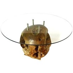 Our Teak Root Ball with glass top is definitely a head turner. The teak root ball has been dug up from the ground, cleaned and sanded. The glass top connects to the ball with stainless steel fasteners. The clear coat brings out the beautiful colors and accents the unusual wood grain. No two are alike so you will definitely own a one of a kind table. This teak root dining table embodies the quality craftsmanship and unmatched style you've come to expect from us.
