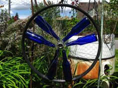 Upcycle your old bottles and bike wheels by making a gorgeous garden display.