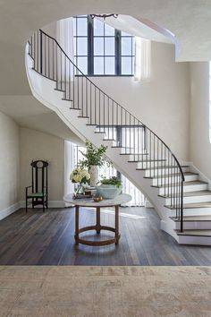 A round wood and marble table sits in the center of a foyer in front of a curved. A round wood and marble table sits in the center of a foyer in front of a curved white staircase ac Luxury Staircase, White Staircase, Winding Staircase, Entry Stairs, Staircase Railings, Curved Staircase, Staircase Design, Staircase Ideas, Staircase Decoration