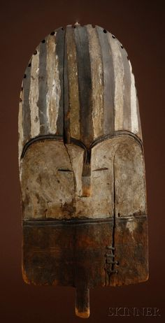Rare African Carved Wood Mask, Mbole, the shield-like form with slightly concave back, narrow pierced eyes under concave arched brows, narrow nose with central indentation, the forehead with grooved and painted stripes, remnant white pigment and pyro-engraved details, handle from the bottom, old repair, old tags on reverse, ht. 14 in.