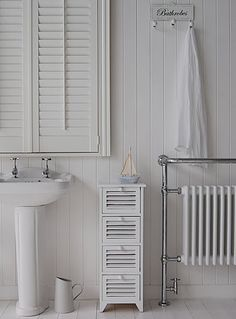A Wooden Slim Bathroom Cabinet In A White Painted Finish With Four Shutter  Style Drawers.