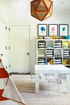 Modern playroom boasts an orange geometric pendant lined with burlap hanging over a white chunky play table lined with Lou Lou Ghost Chairs atop a Jute Chenille Herringbone Rug.
