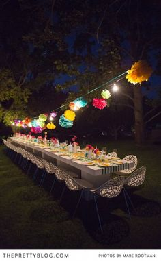 coloured pom poms pack a colourful punch and look pretty good when lit - hung along horizontal ceiling supports with bistro lights and paper lanterns