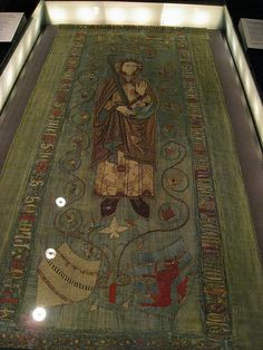 Tomb covering from Skokloster Church, Uppland, Sweden. Photo by Catrijn vanden Westhende. Described as the only medieval tomb cover to survive intact, the fabric is a thin green silk with a backing of blue linen tabby. The appliqué figure represents Holmgar [Holmger?] Knutsson [1210s-1248], [Swedish noble & claimant to Swedish throne] but was made >200 years after his death. Silk appliqué with gold and silver embroidery.