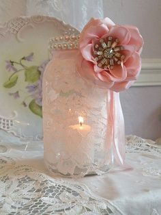 mason jar covered with lace, lined with pearls, an adorable flower and some ribbons. drop in a candle to top it all off...baby shower fabulous!